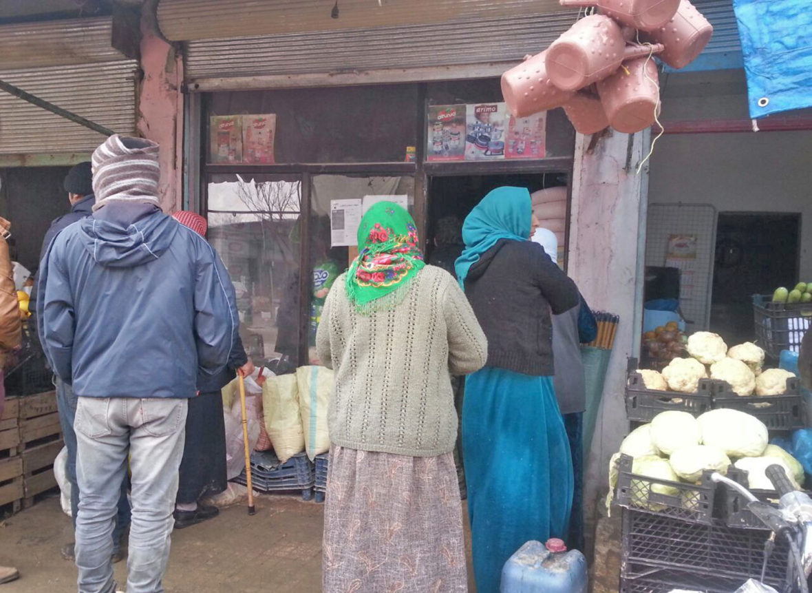 Displaced Syrian families wait in line to redeem Concern food vouchers