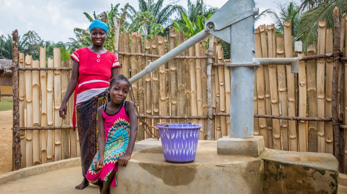 A woman in Liberia stands with her daughter at a water pump