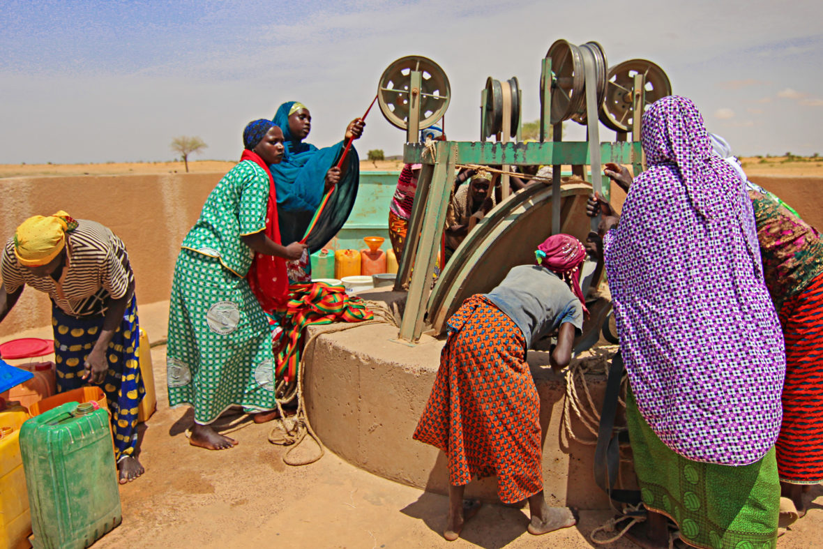 women lift water from a well in Niger