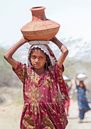 Girl in Pakistan carries water home