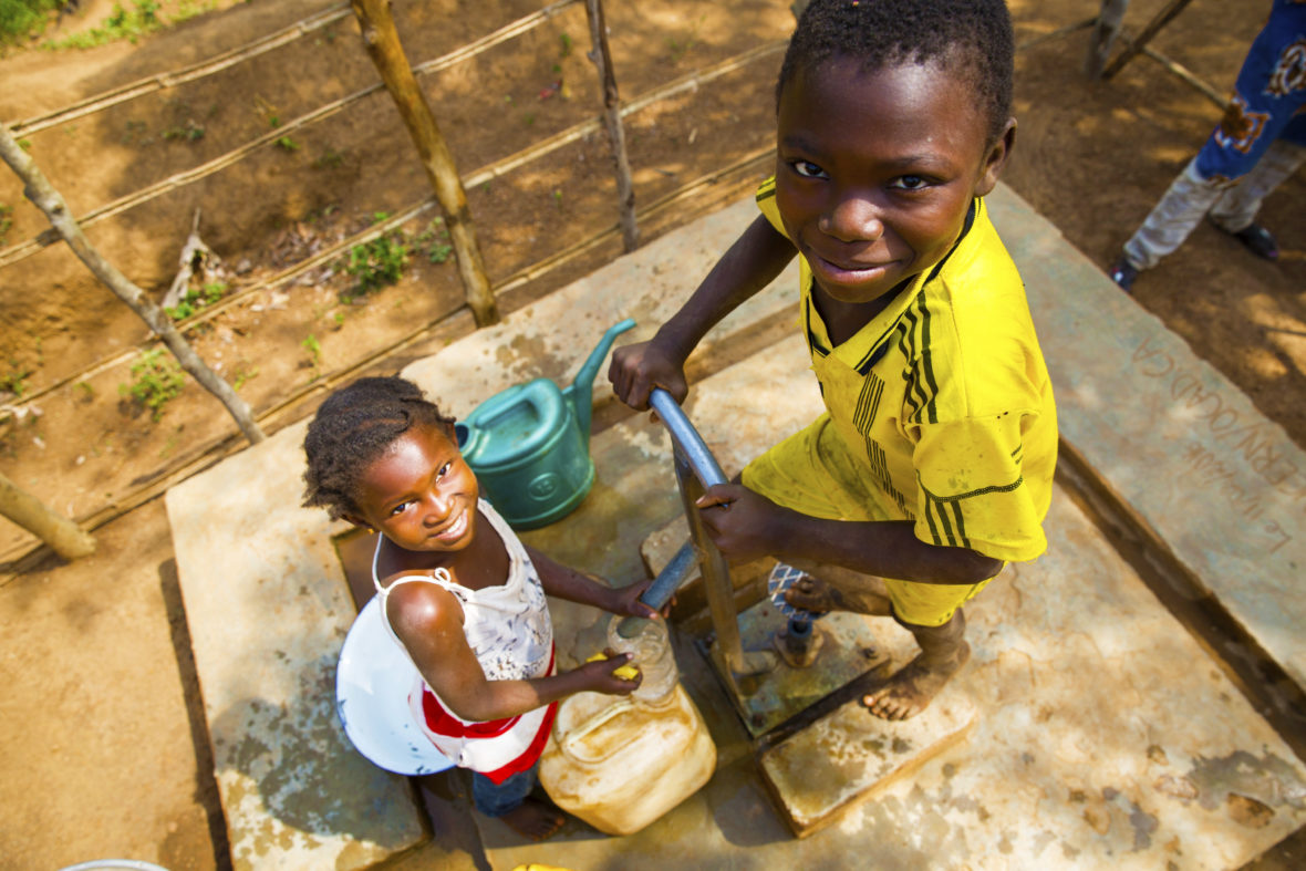 Two children pump water
