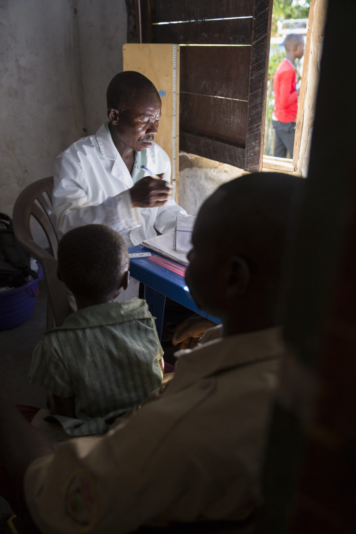 Dbuyu Kalembe, a medic, sits in his clinic with a man and a young boy