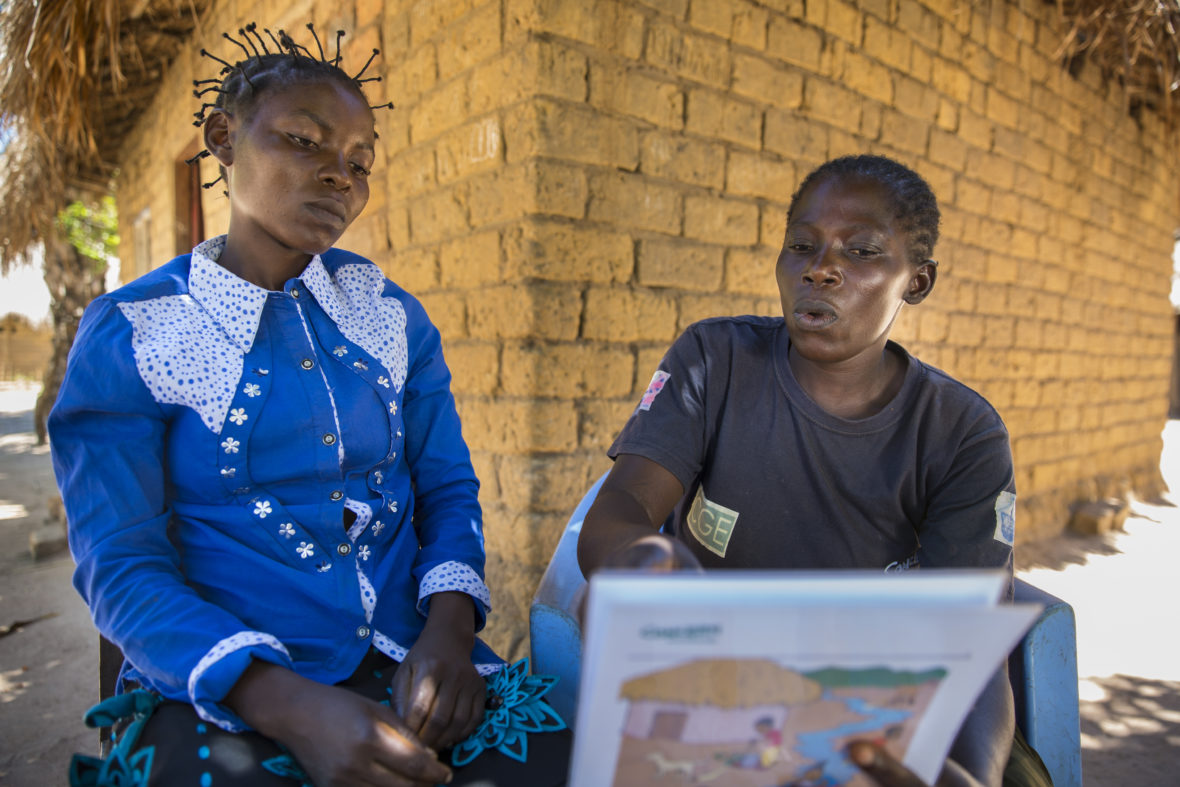Joelle and Adele go through a hygiene flip chart outside Joelle's home in DRC