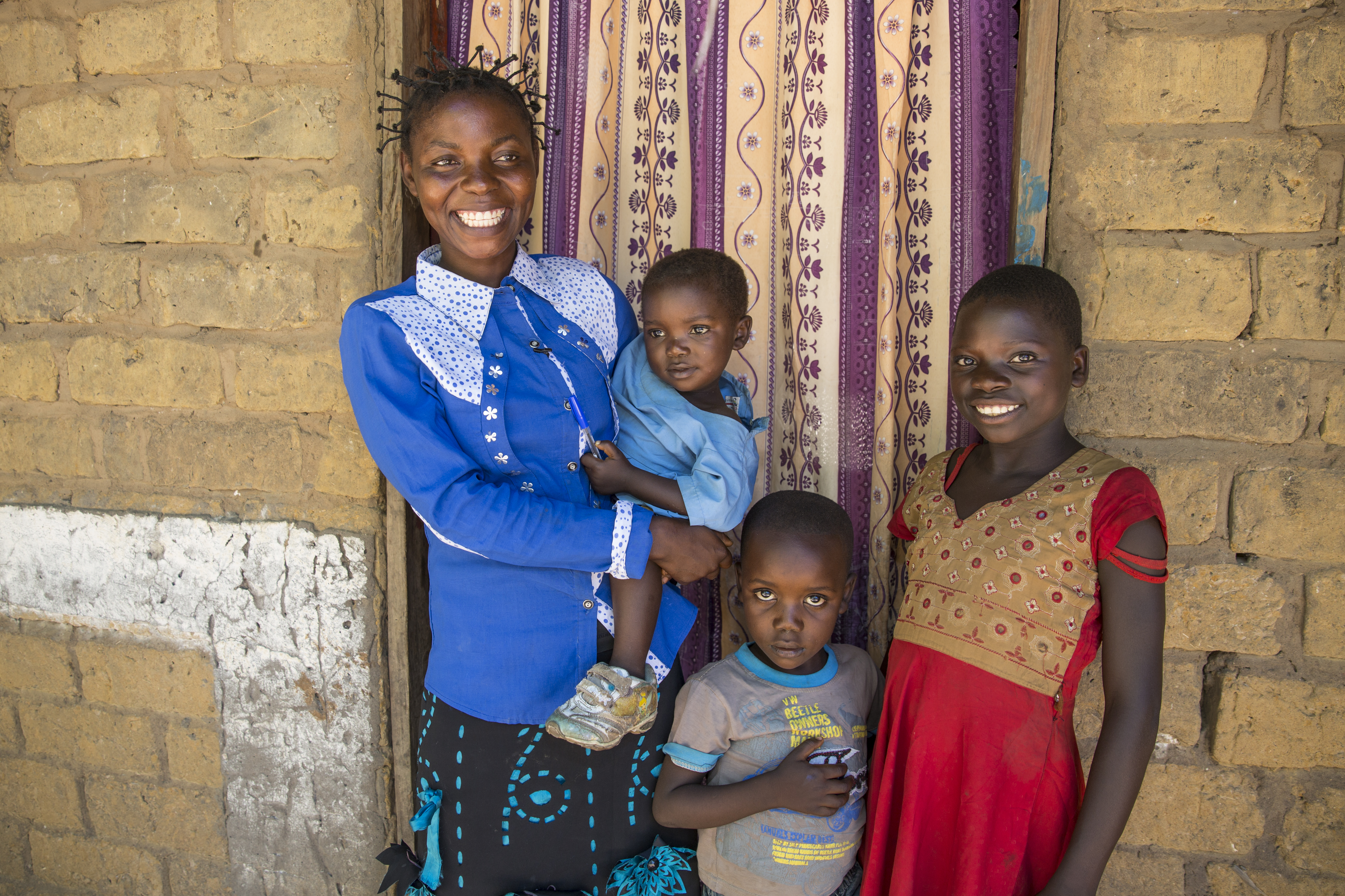 Joelle Inamulongo stands in the doorway of her home in DRC with her 3 children