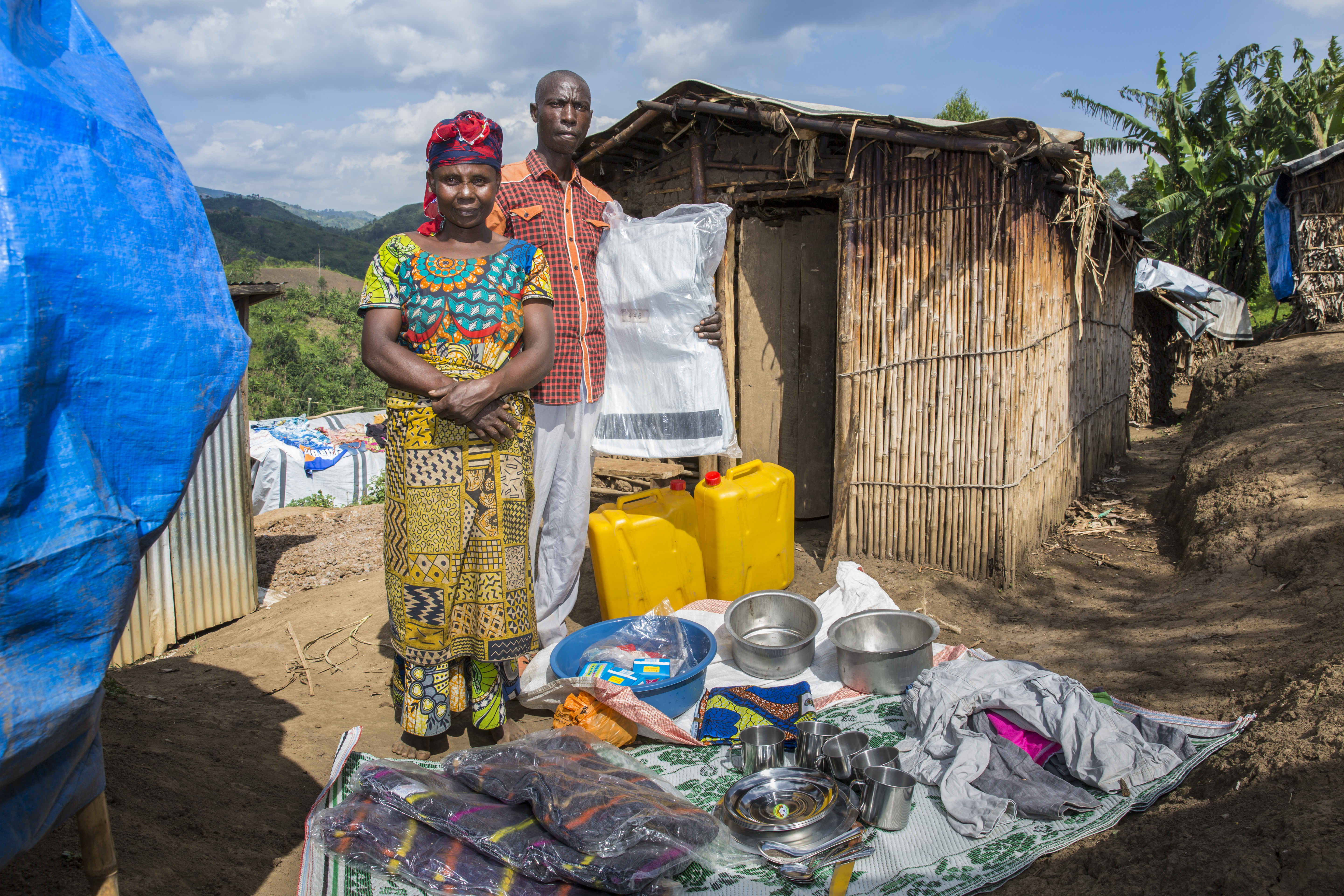 A couple standing outside a temporary shlter on a hillside in DRC with a set of household goods given to them by Concern