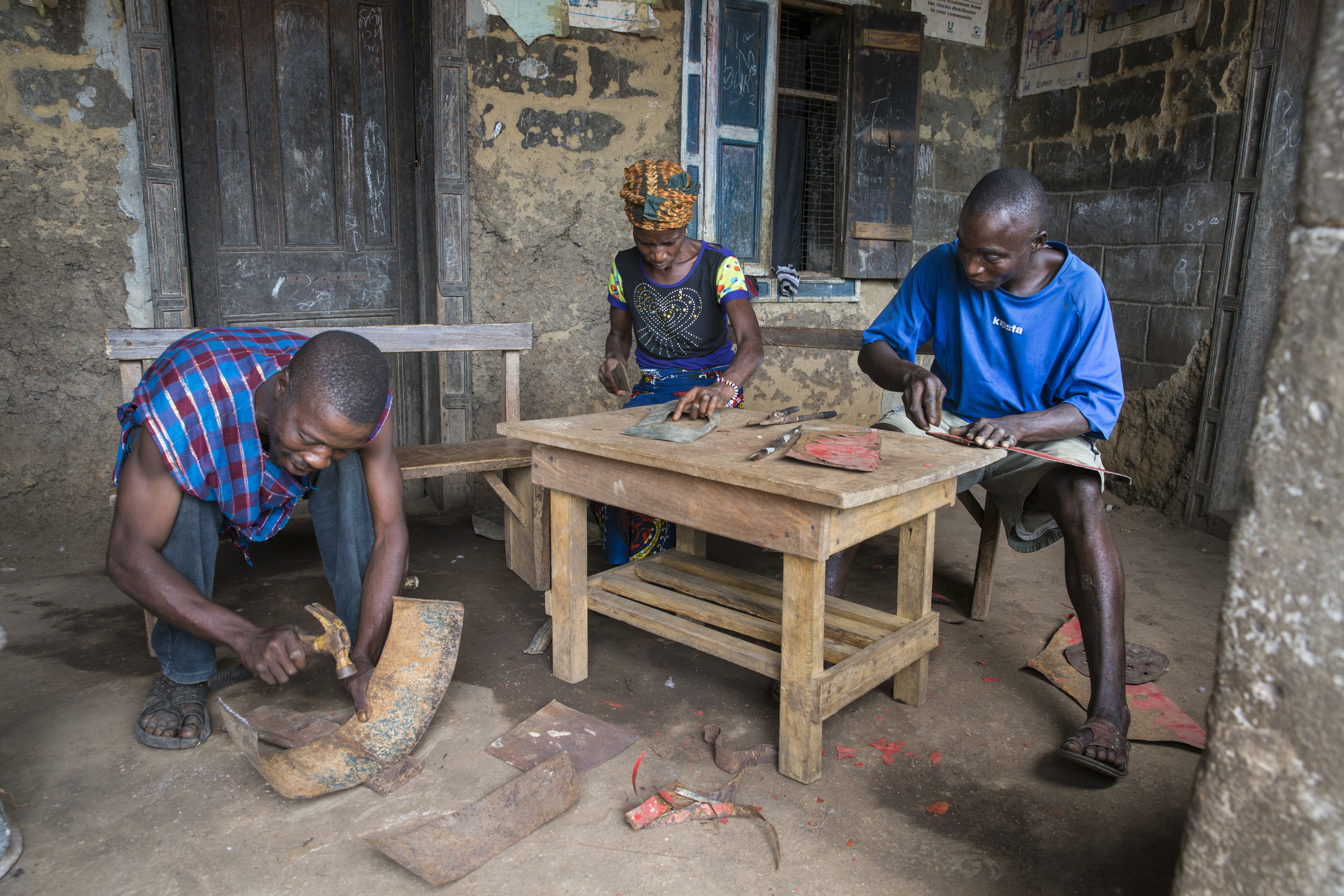 Three people work on scrap metal to make eco stoves.