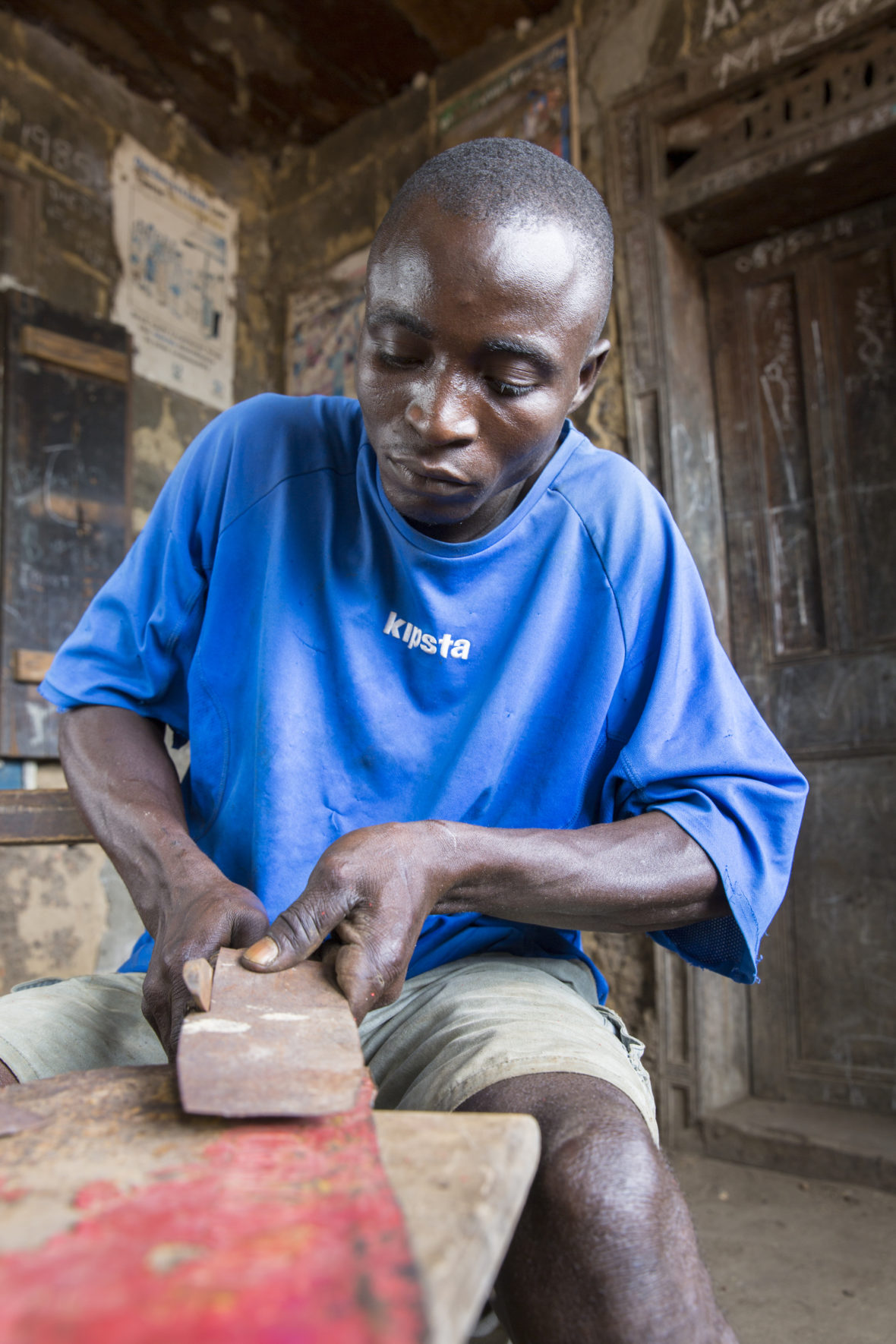 Man sitting at table, working on shaping a piece of metal with a tool