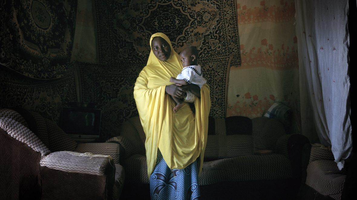 Nigerien woman stands inside her home