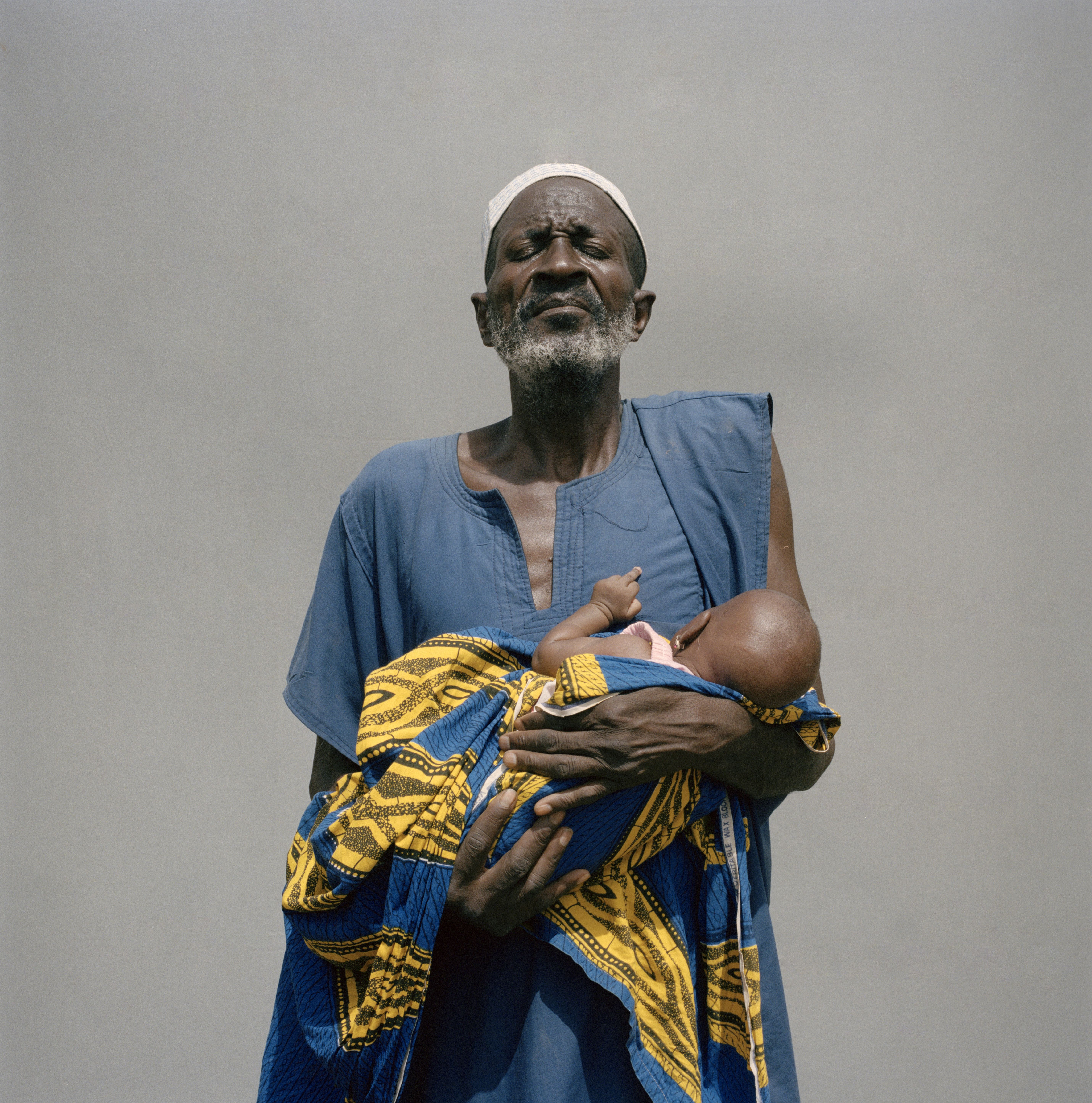 Elderly Nigerien man sits in a seeds store with his stick