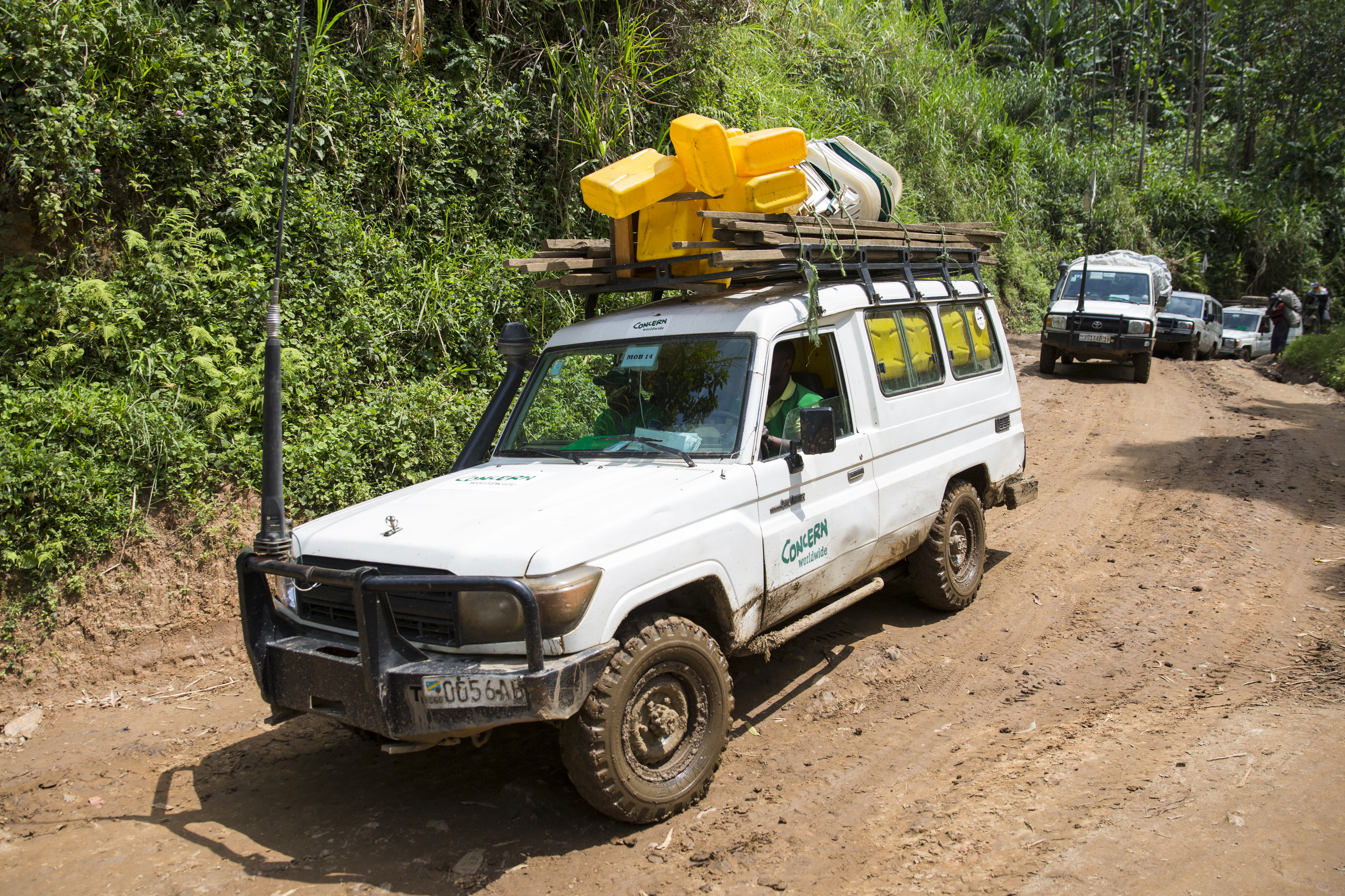 Concern Land Cruisers on a narrow dirt road
