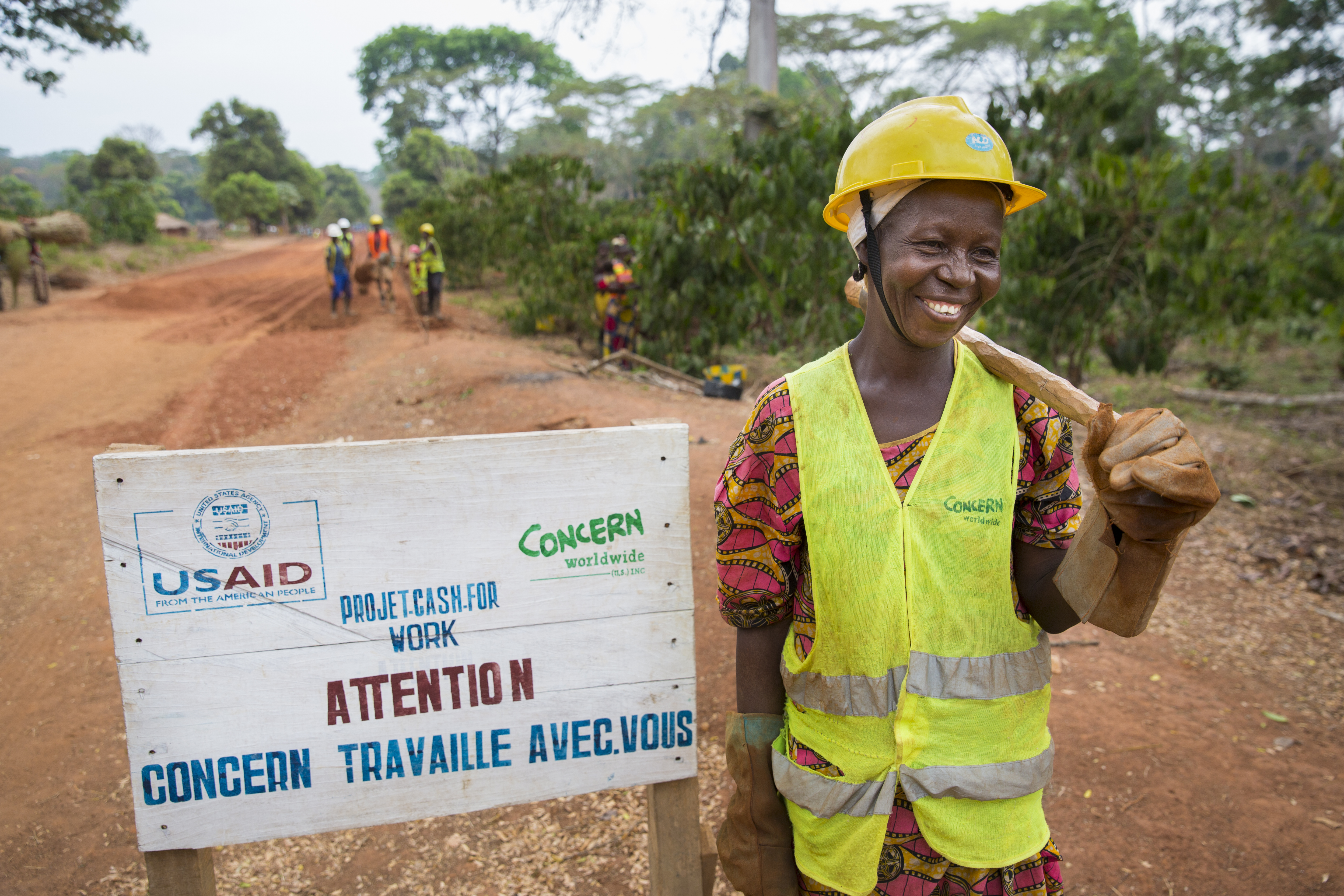 Smiling woman with hard hat and pick axe, standing on road beside a sign
