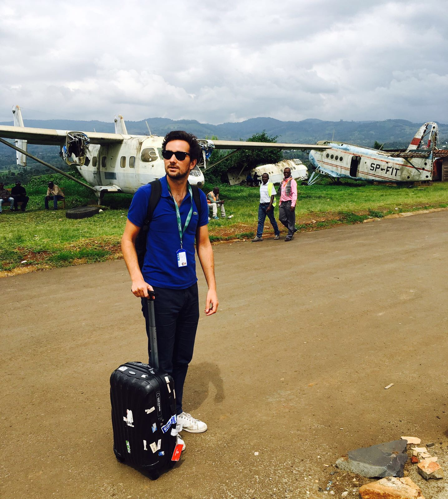 Concern CD stands on dirt airstrip in DRC, with broken planes in the background.