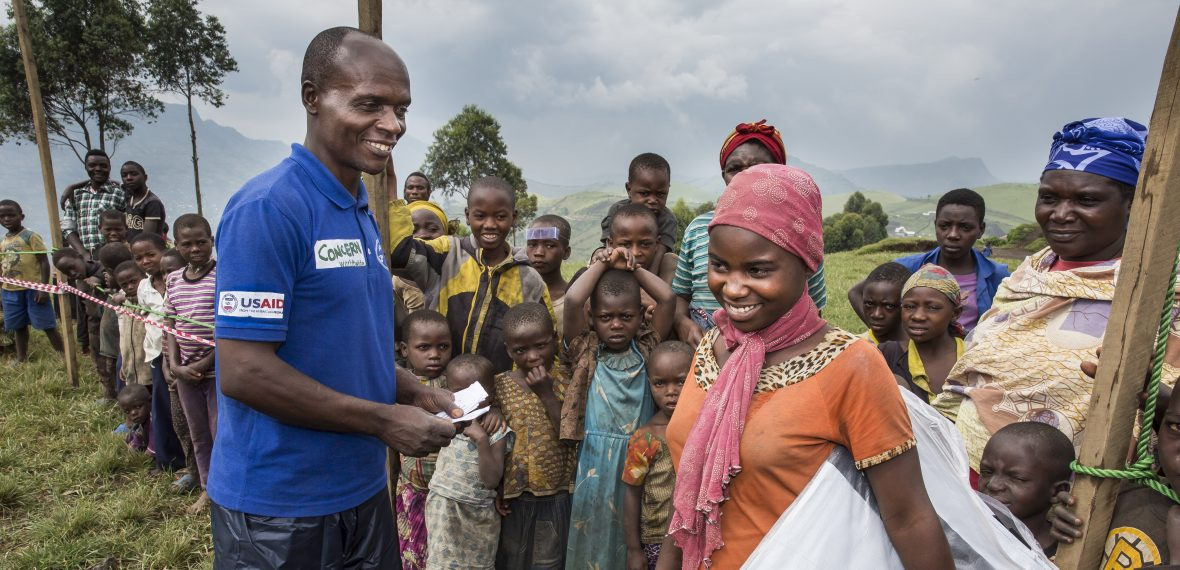 Thanks to foreign aid, Concern worker distributes a tarpaulin.