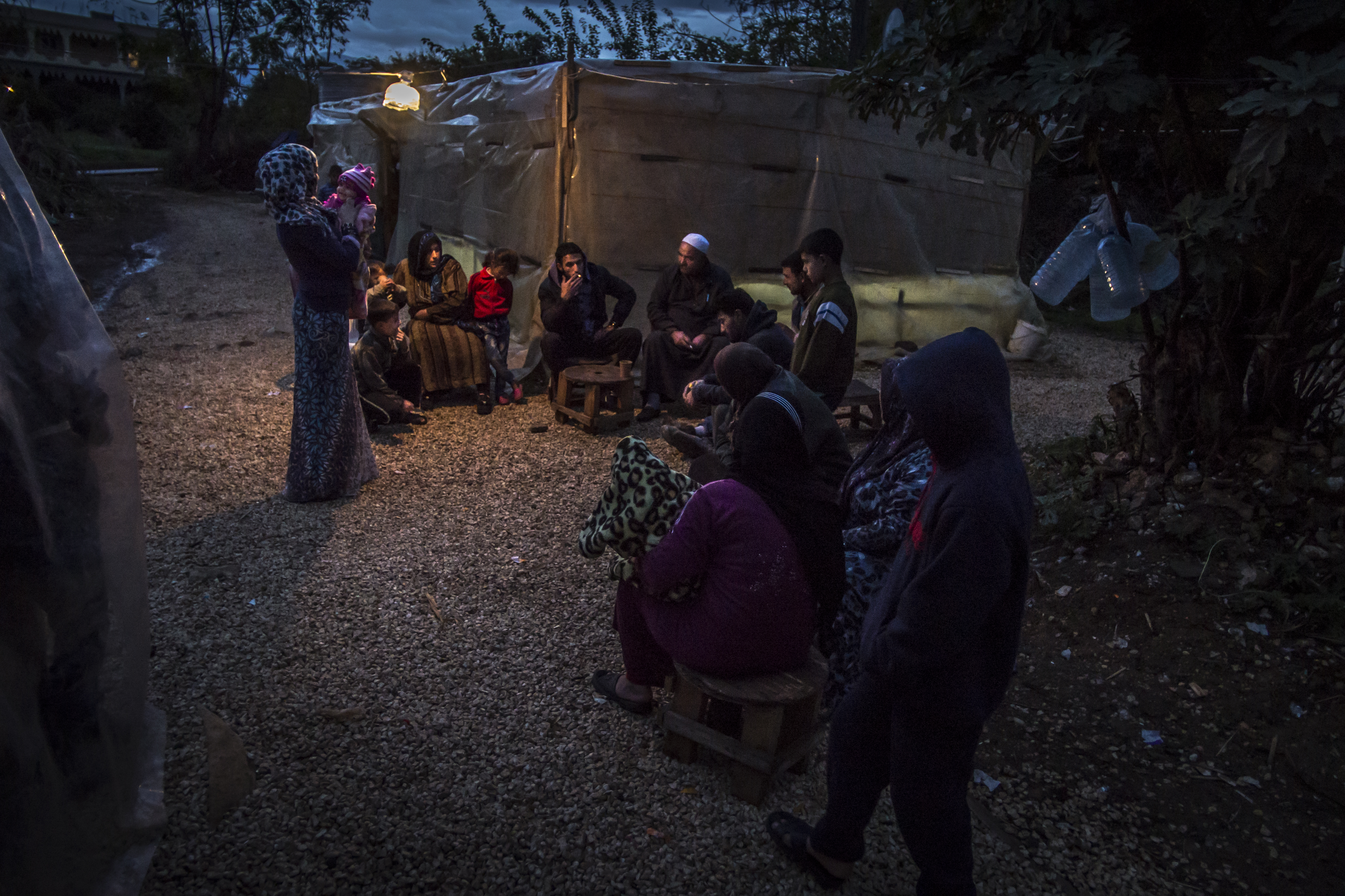 A group of people sitting / standing around a makeshift tent at night.