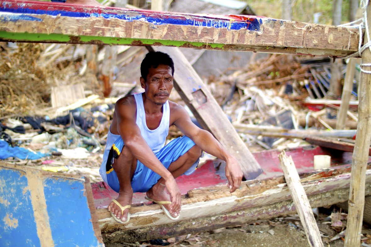 Boat captain sits in wreckage of his boat after a typhoon.