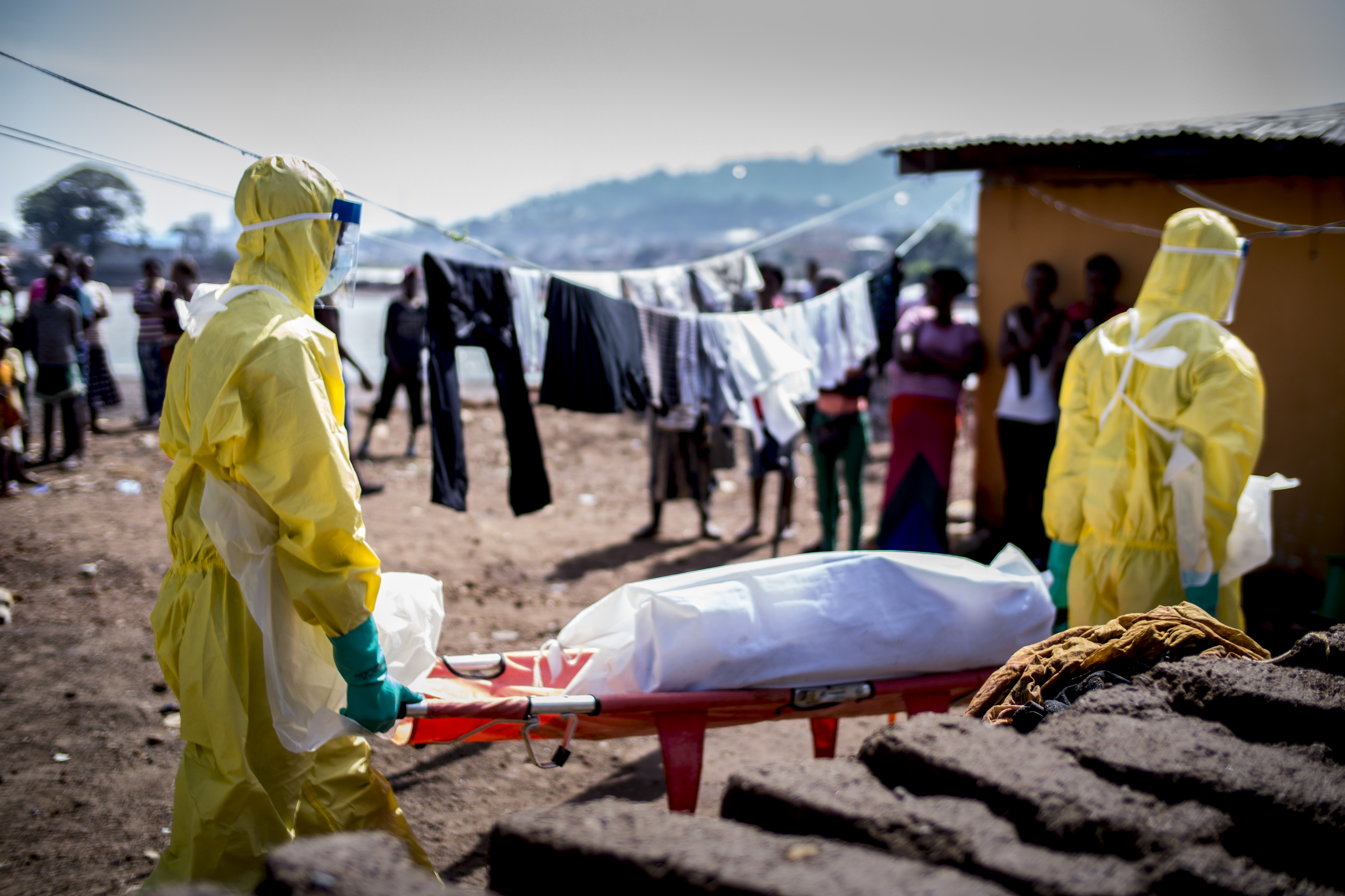 Two men in protective outfits carry the body of an Ebola victim.