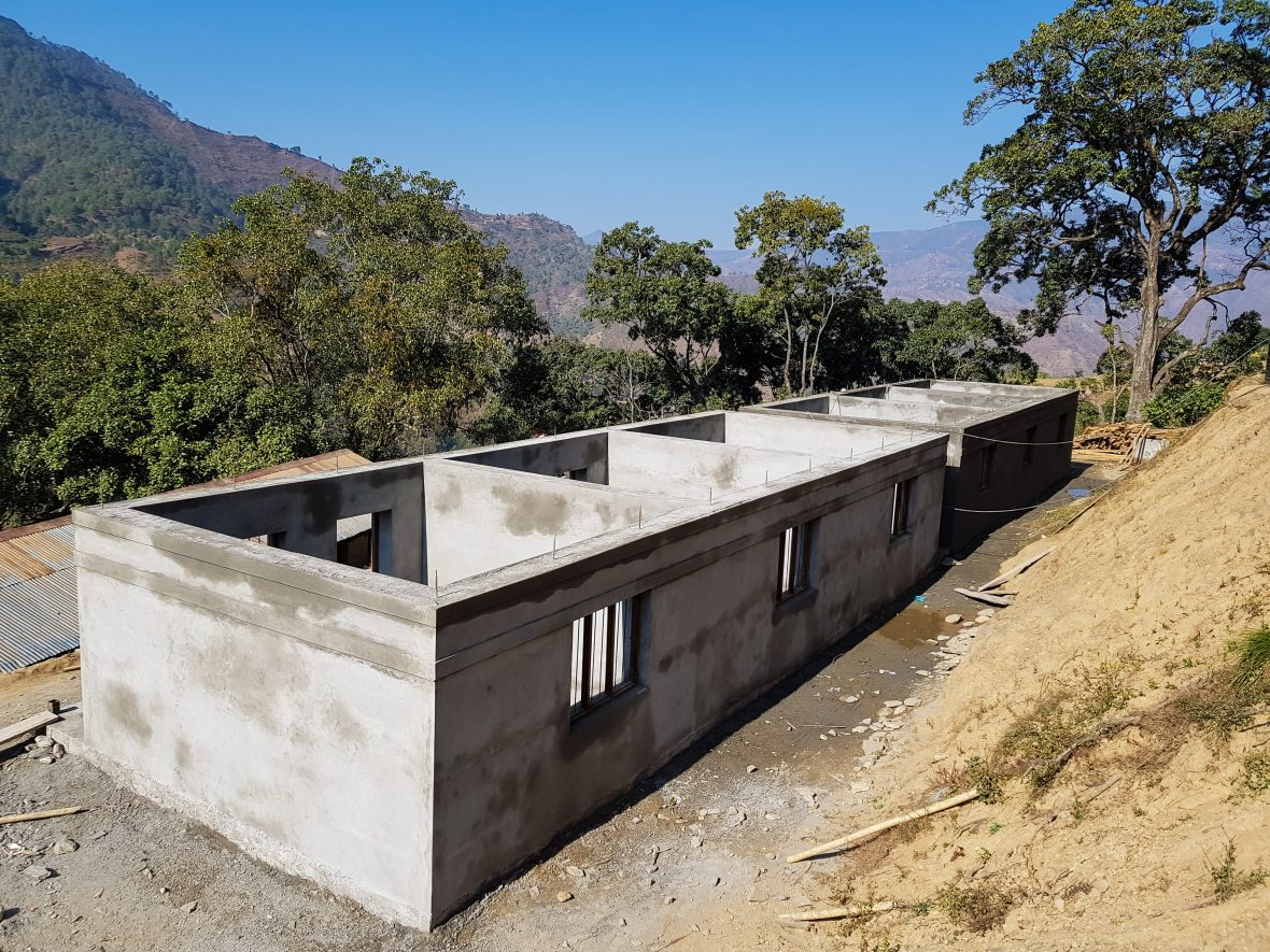 A concrete school built to roof level on hillside