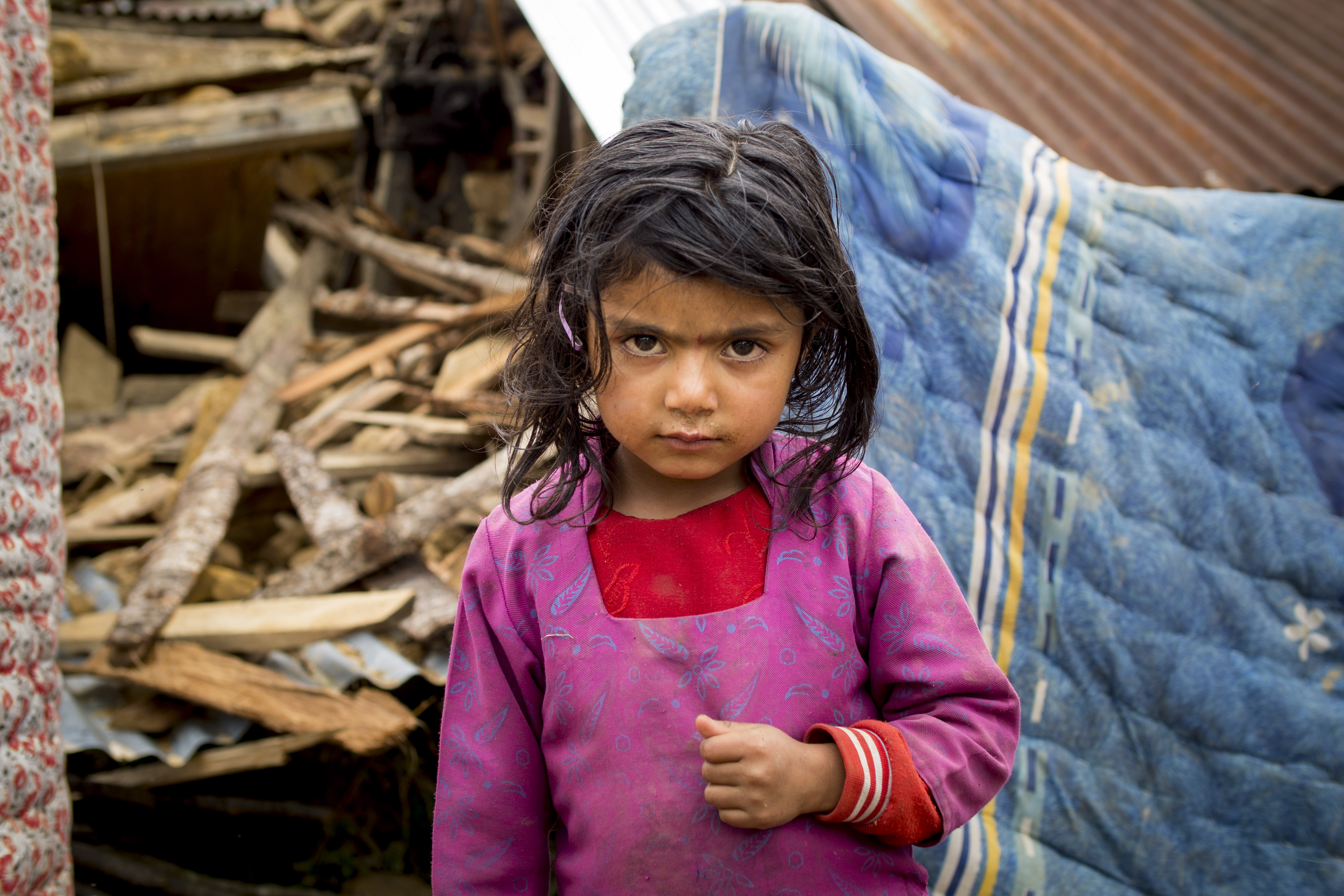 Young Nepali girl stands in front of ruins of home knocked by earthquake.