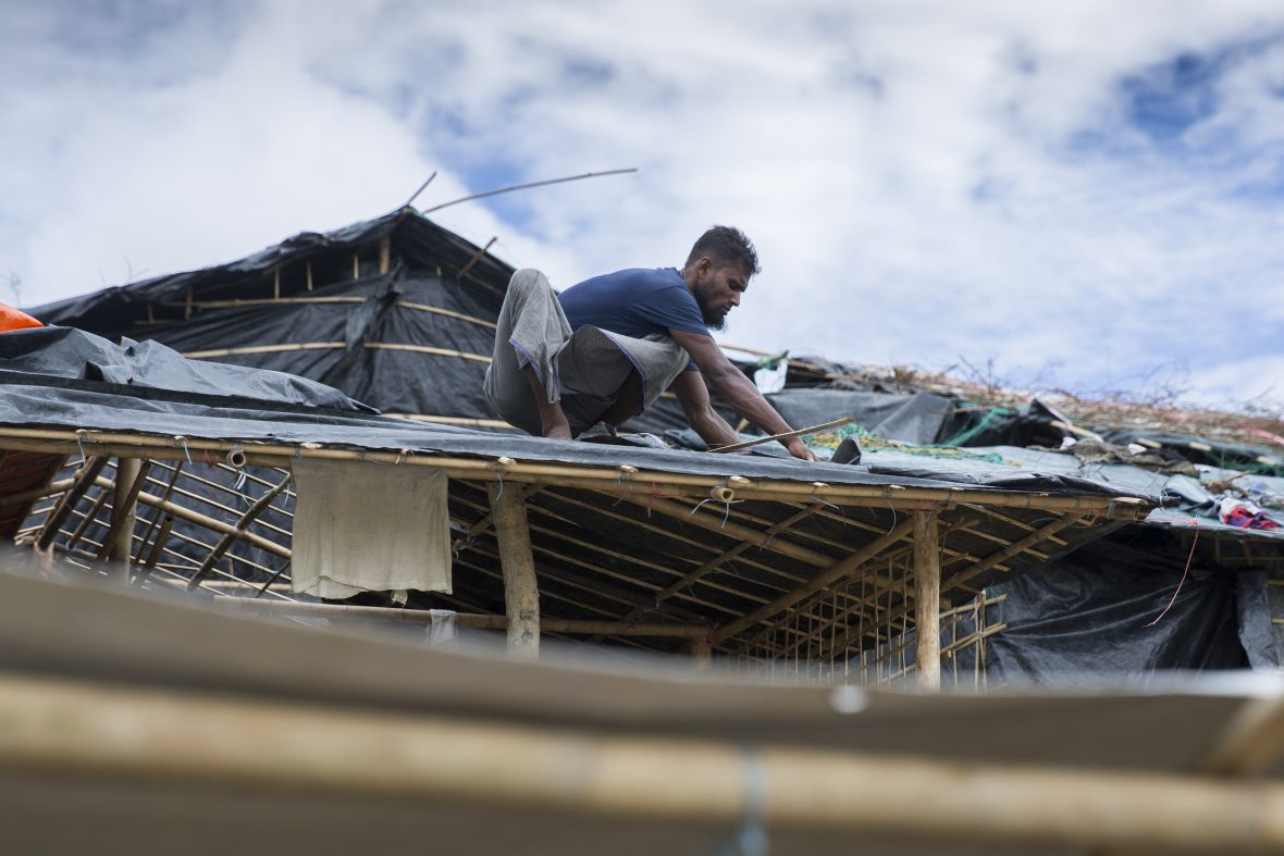 Man on roof of temporary shelter, fixing it