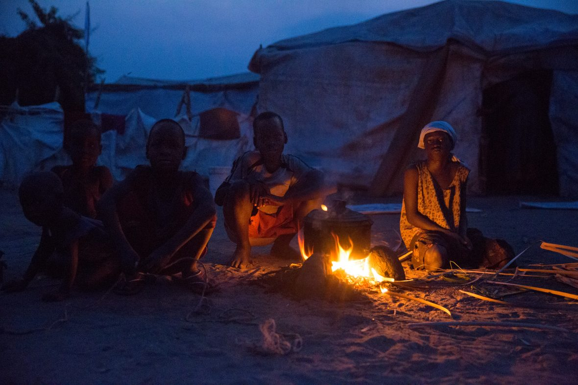 Displaced people huddle at night by a fire in South Sudan