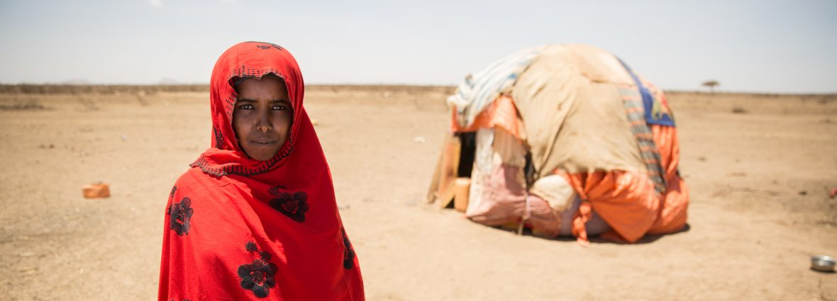 Woman stands by a rough desert shelter