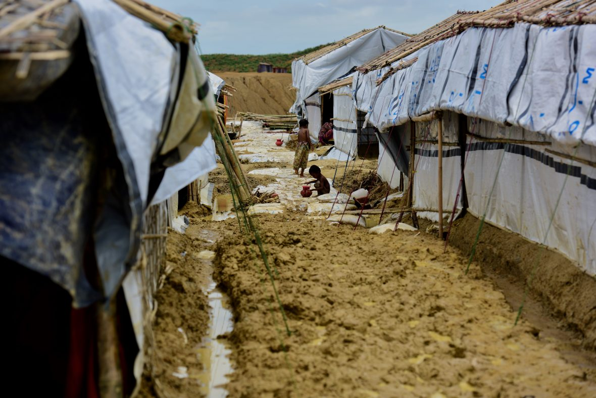 Tents surrounded by mud, with young child.