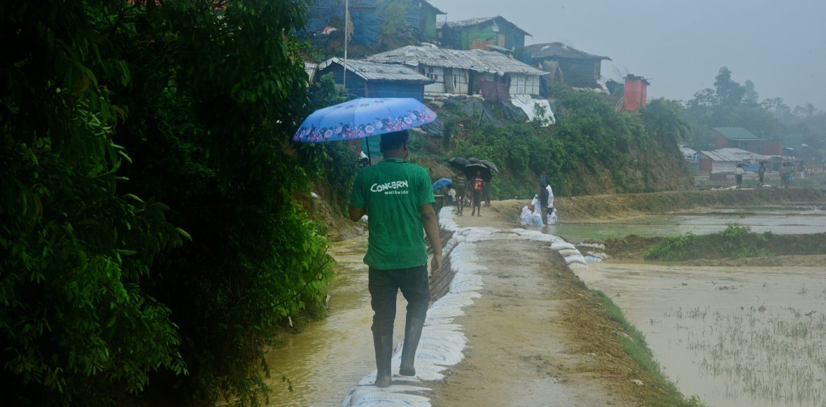 Concern staff member from behind with umbrella Cox's bazar