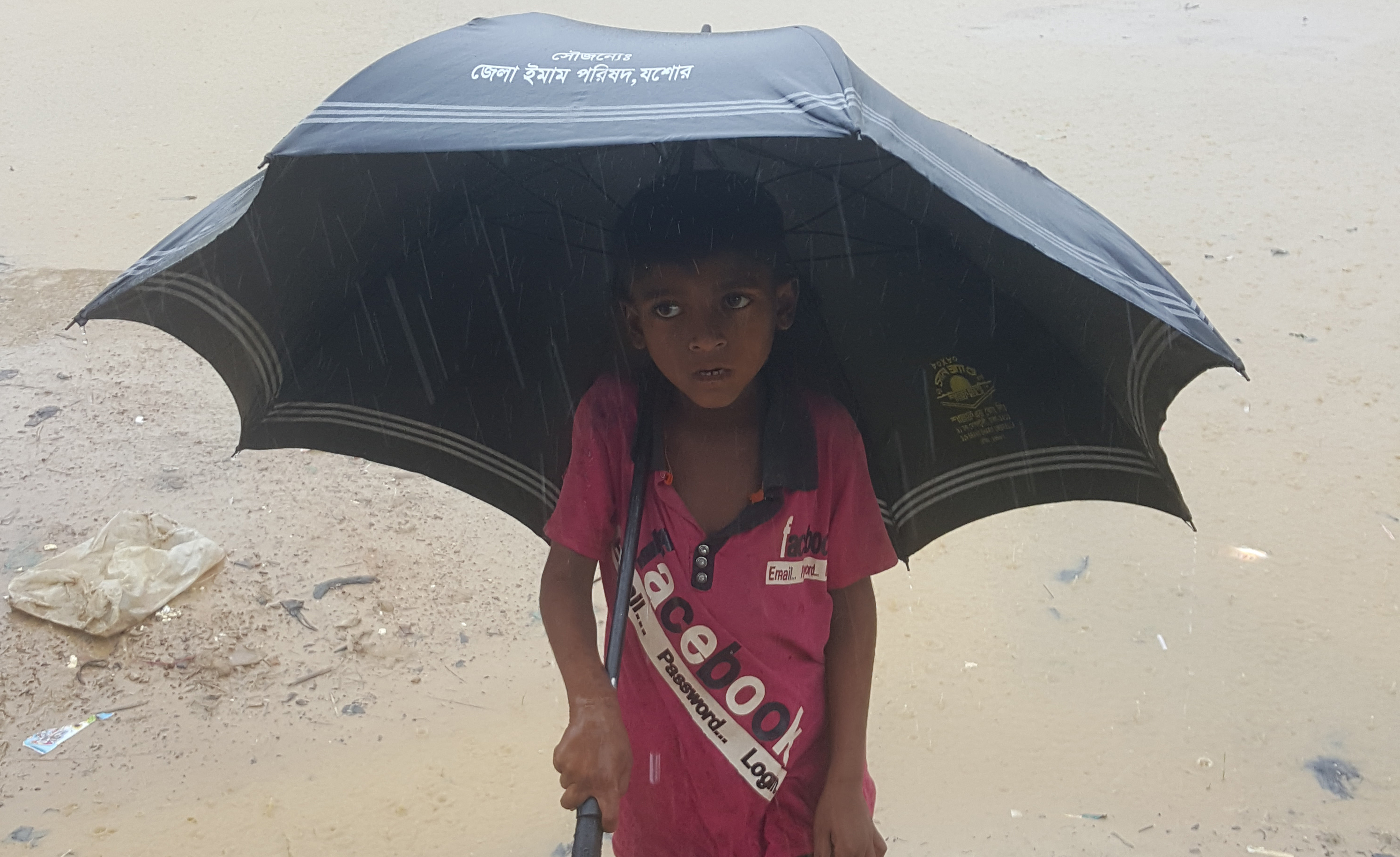 Child in mud and rain with umbrella