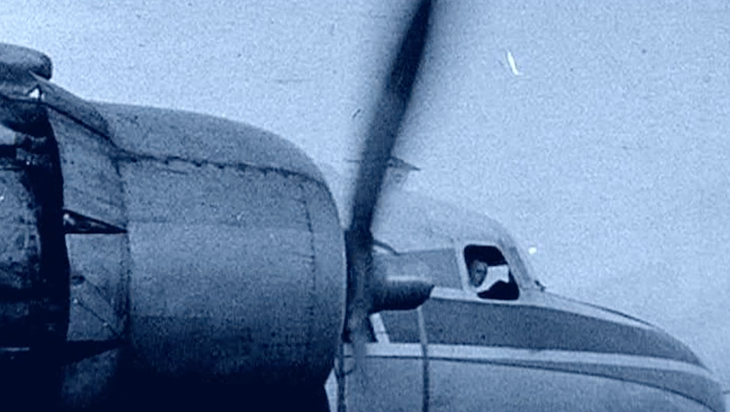 propeller plane with pilot looking out window