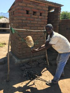 A man washing his hands with a tippy tap