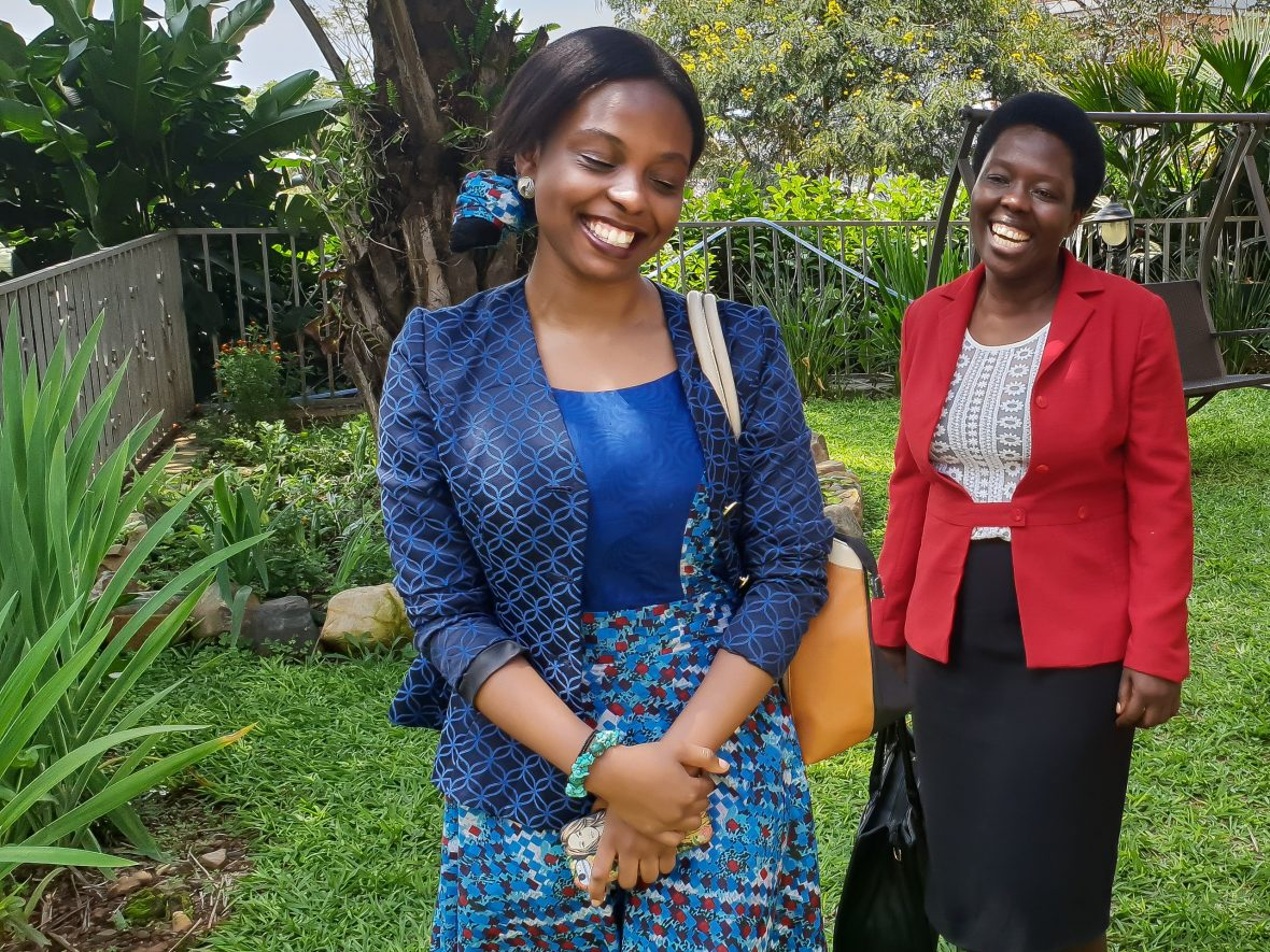 Aline Joyce Berabose and her mother, Marie-Ange in a garden in Kigale, Rwanda, laughing.