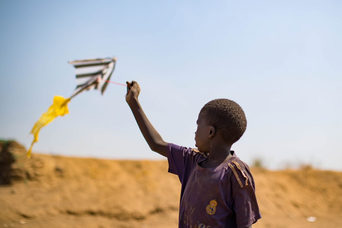 A child flies a home made kite on the streets of Juba's PoC, South Sudan.
