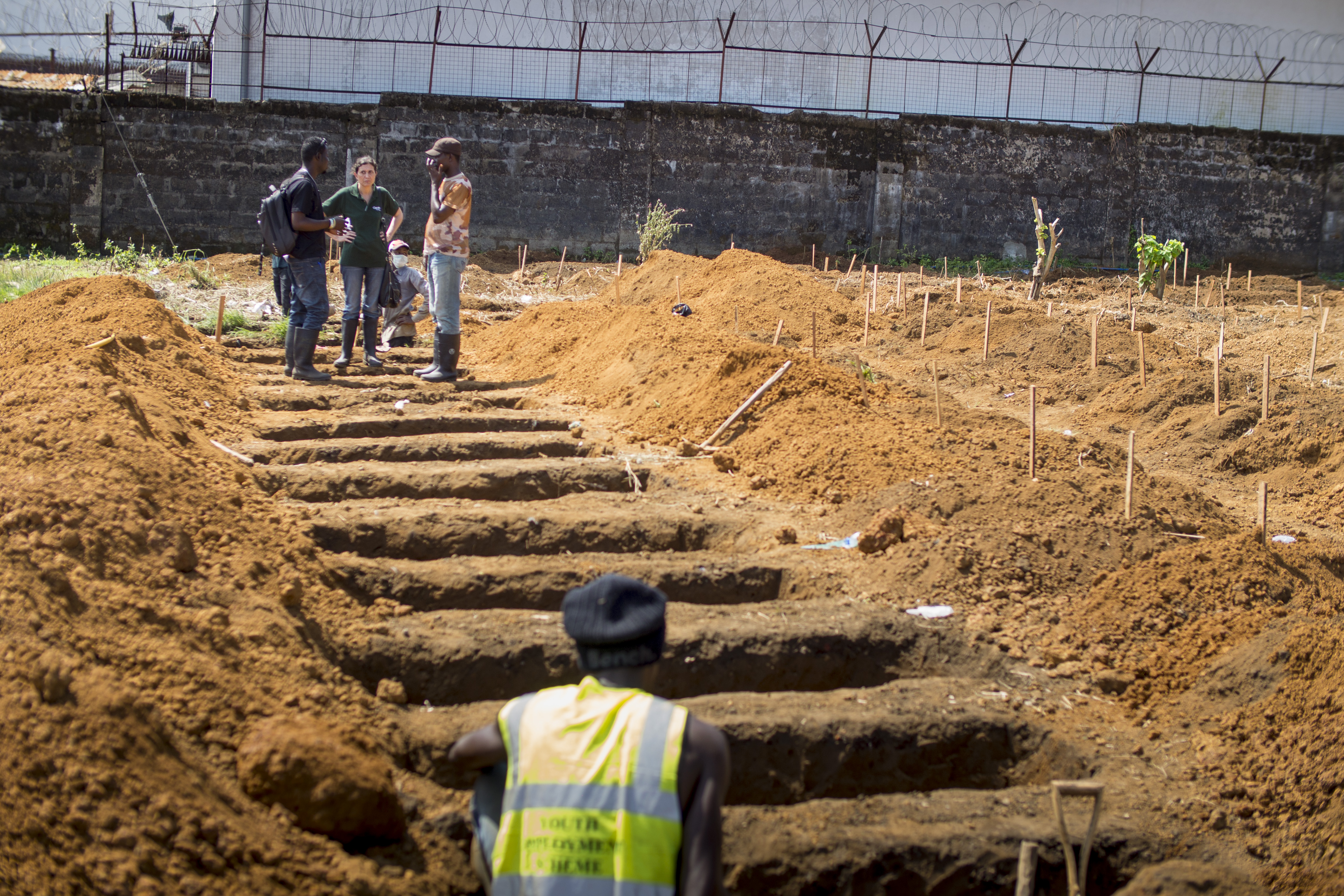 Fiona McLysaght, Concern Worldwide's Country Director for Sierra Leone, talks with members of Concern's burial team at Kingtom cemetery in Freetown.