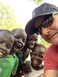Niall O'Brien surrounded by smiling children in Ethiopia.
