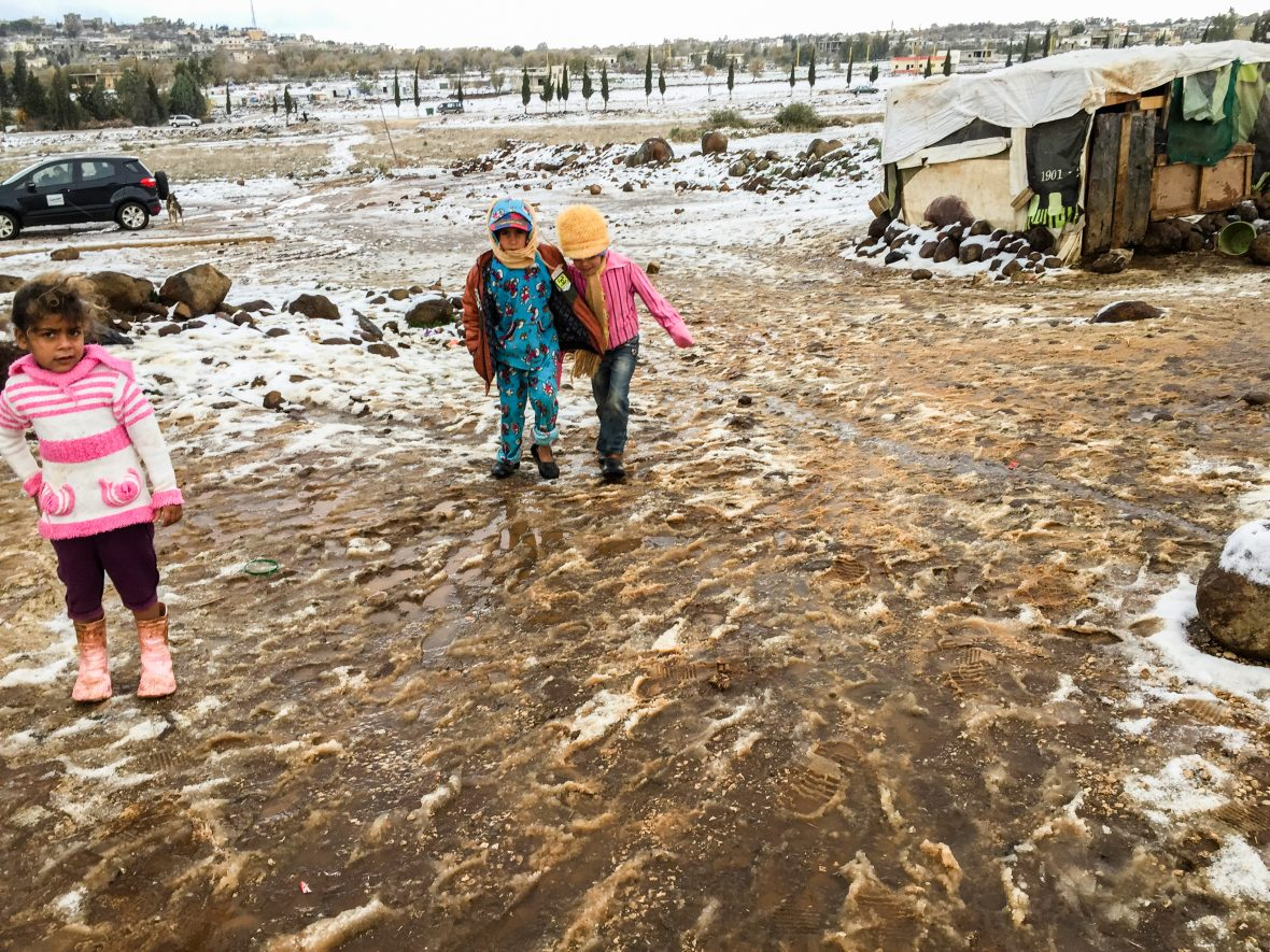 Syrian Refugee children, living in informal settlements in Lebanon wade through the mud caused by storm 'Bladimer'