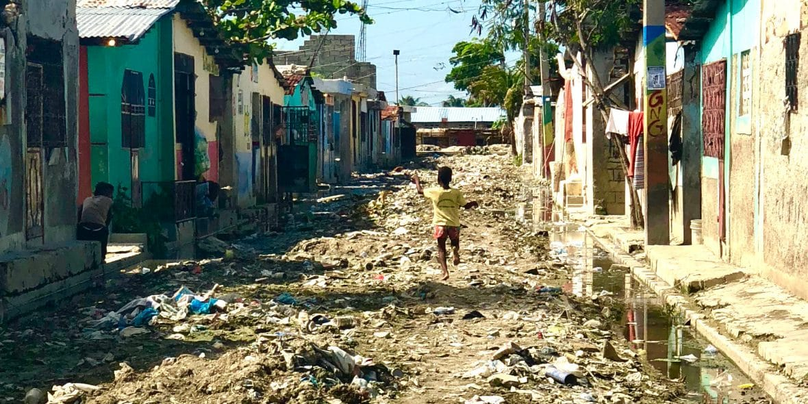 A little boy runs through a garbage-filled street. When it rains, solid waste and trash run down the hills to Cité Soleil, causing flooding, hazardous conditions, and rampant disease.