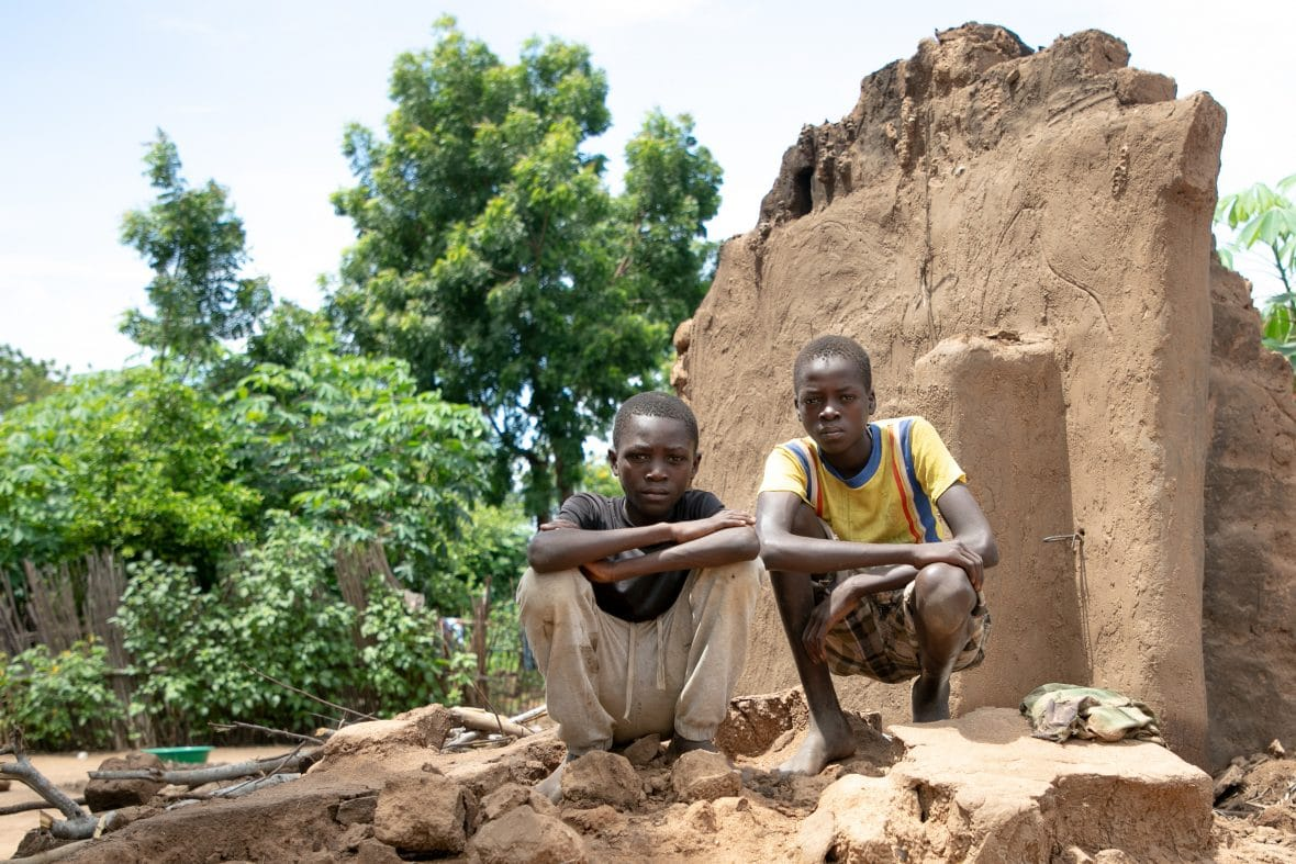Brothers Charity(16) and Fraction (14) standing on what's left of their home.