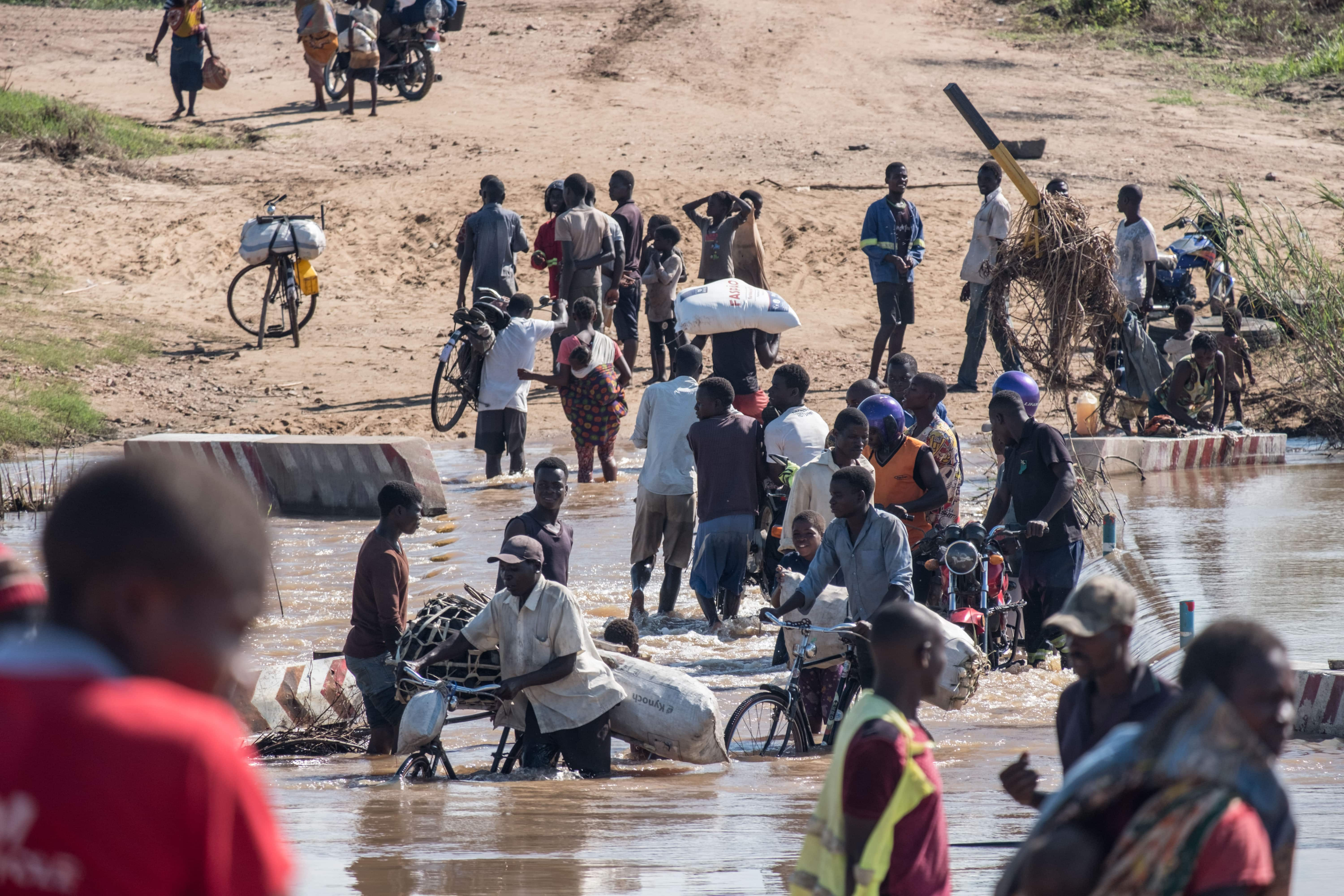 People wade across a river in flood near Nhamatanda, Mozambique.