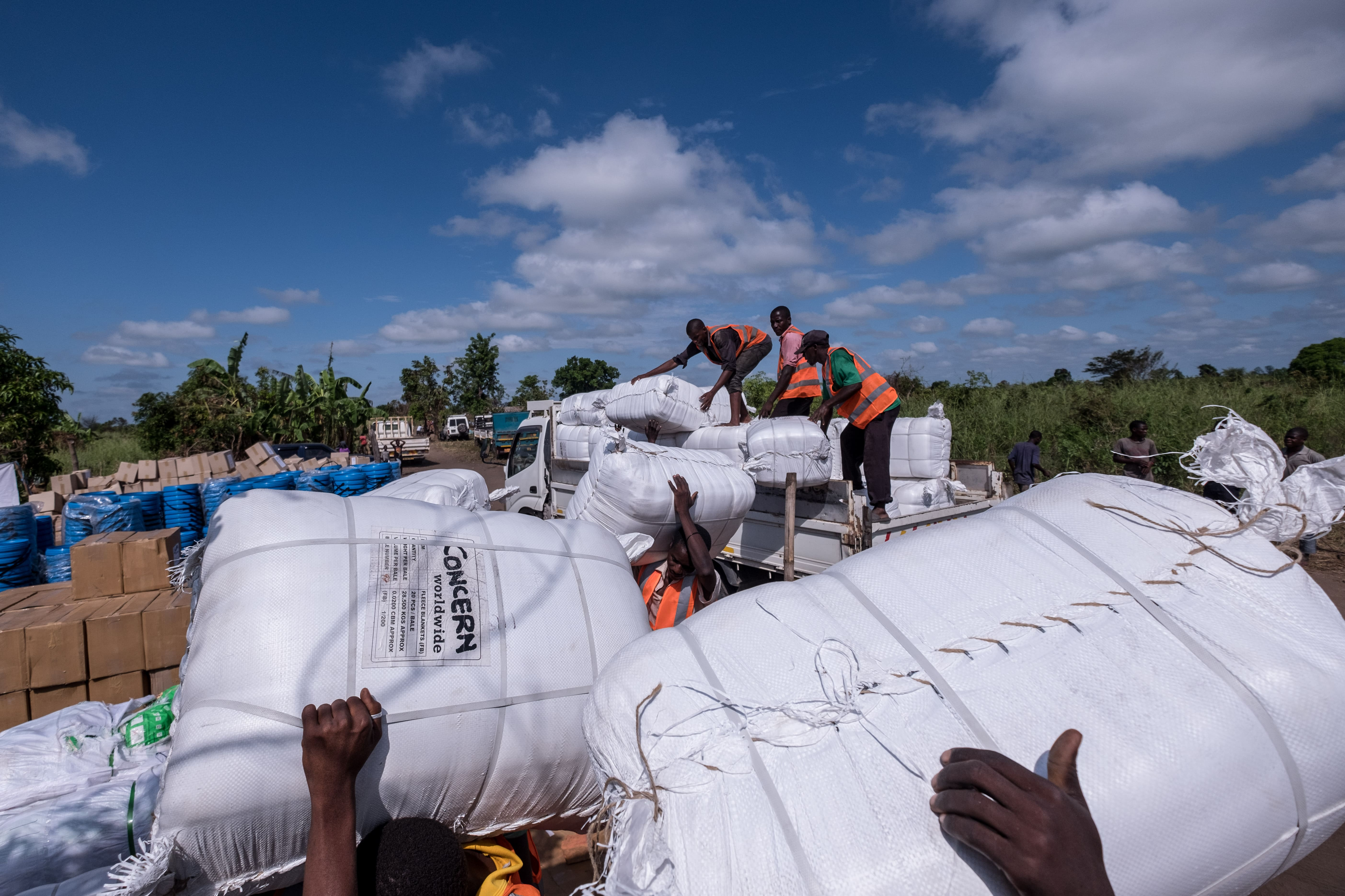 Workers unload bundles of blankets and bedding from a truck at a distribution in Ndeja, Mozambique