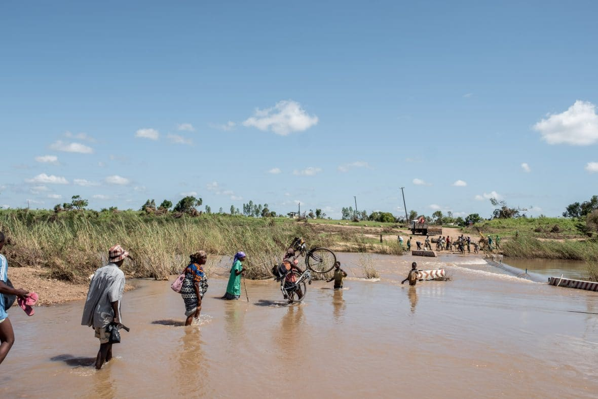 People wade across a river in flood near Nhamatanda, Mozambique