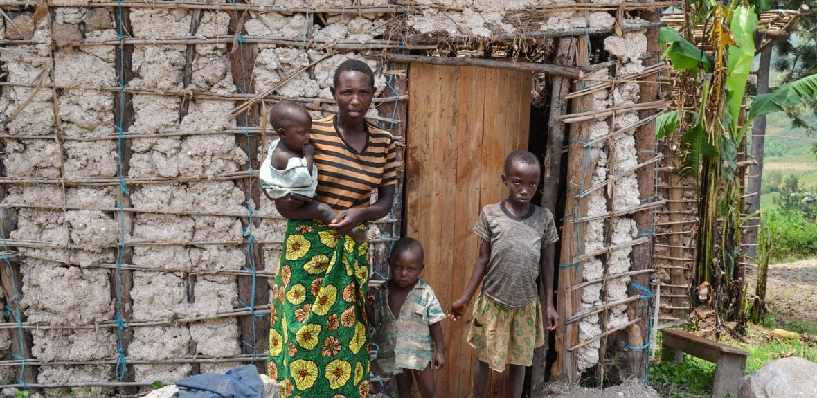 Alphonsine Mukeshimana with her family beside the structure they live in, Rwanda.