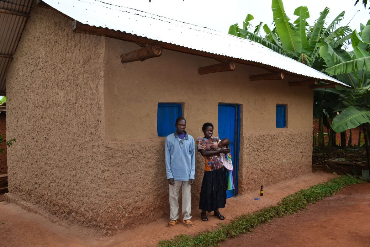Sylvere Ndayambaje, who took part in Concern's graduation program, with his family outside his new home in Rwanda