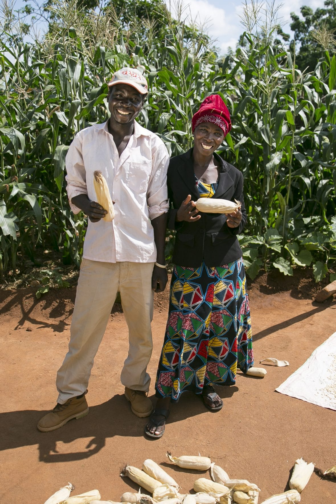 Farming couple in Malawi with maize harvest