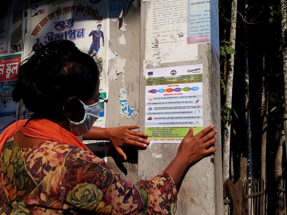 Woman putting up COVID-19 poster in Bangladesh