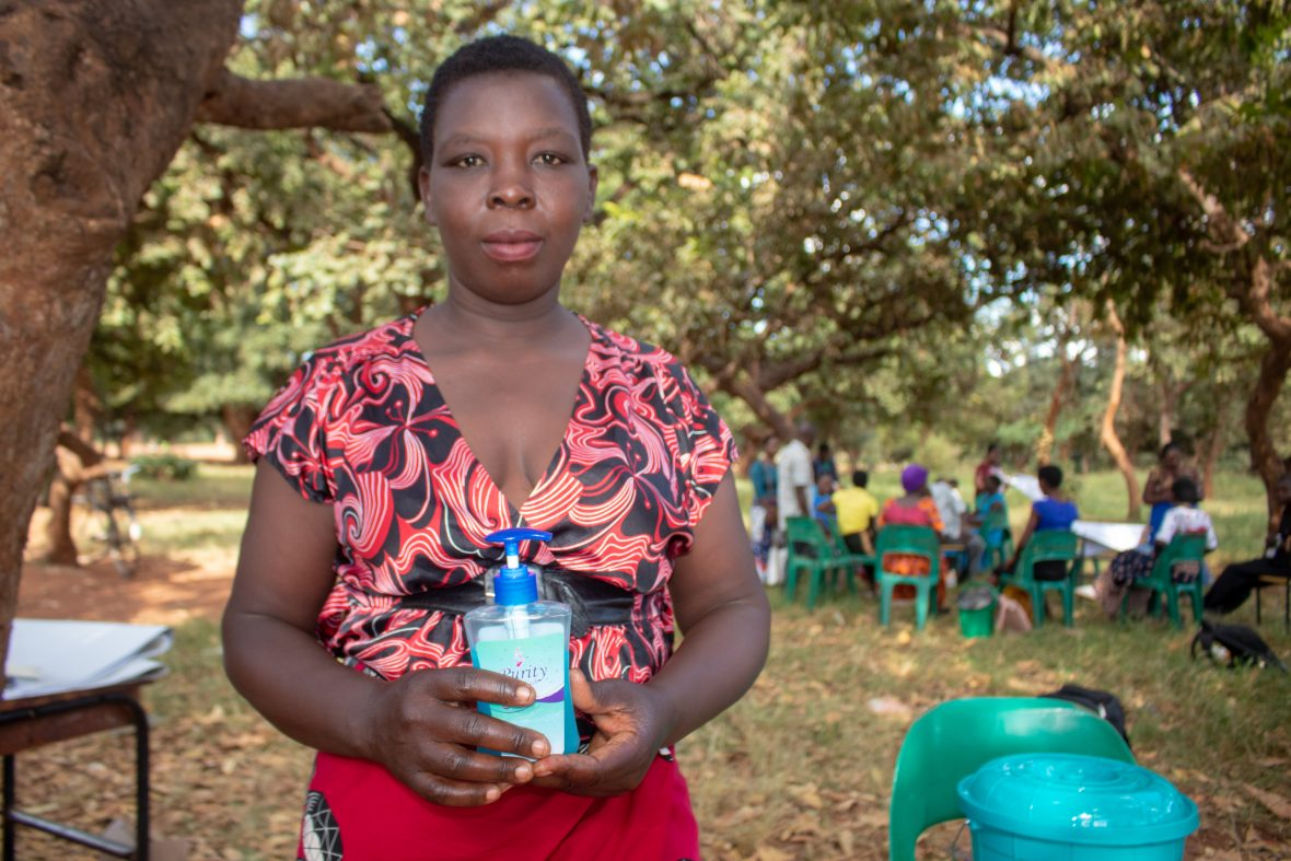 Community health worker holding a bottle of hand sanitizer