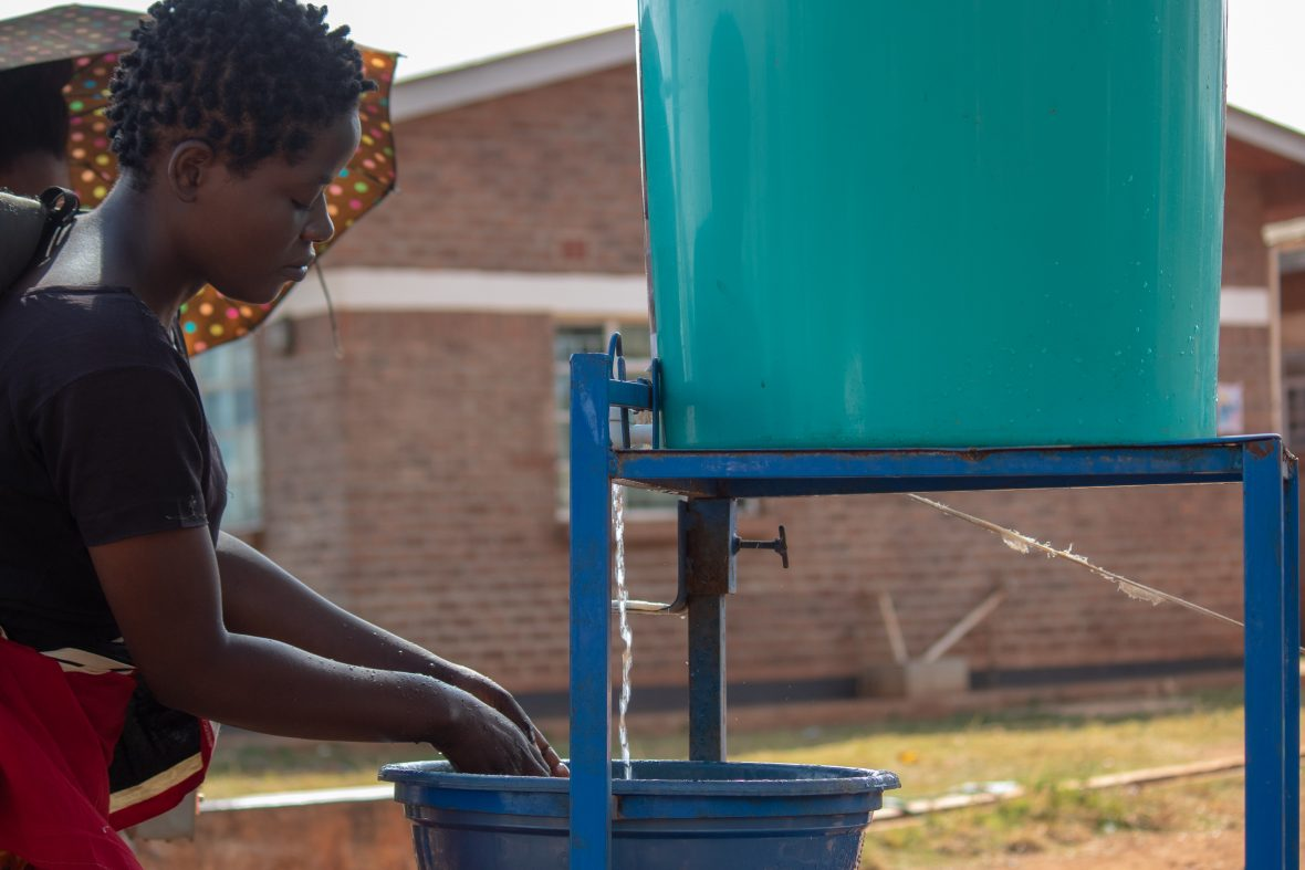 Healthcare worker in Malawi washing her hands