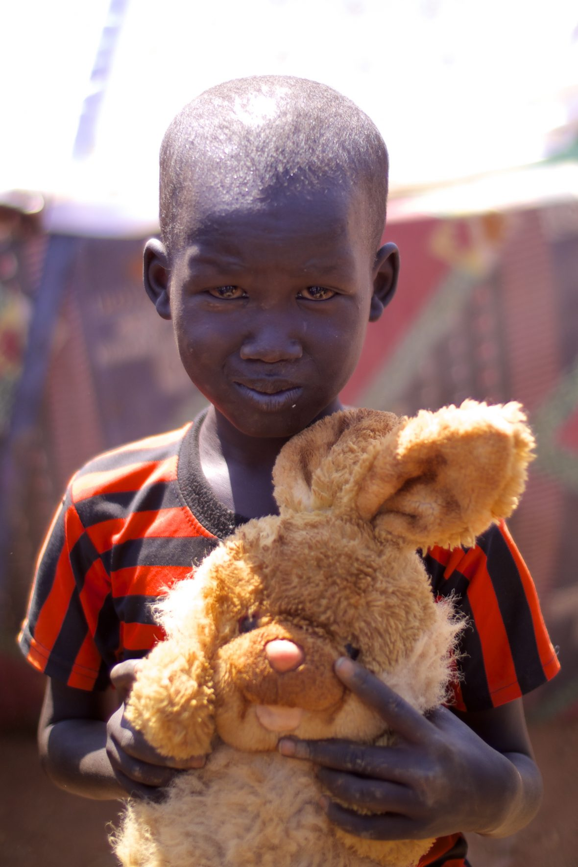 A displaced boy in South Sudan with a furry toy