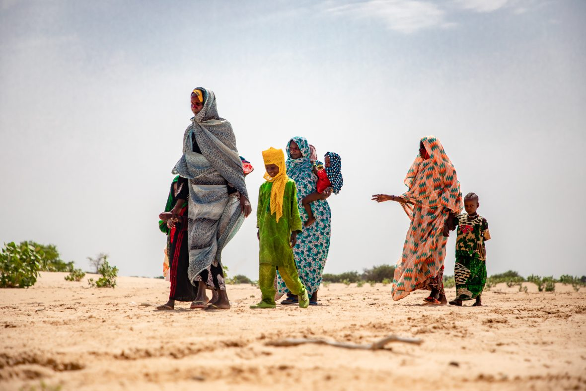 Women and children in the barren landscape of the Lake Chad region.
