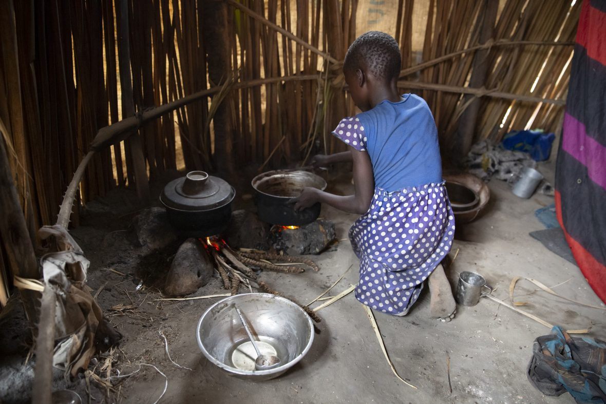A young girl tends a cooking fire in South Sudan
