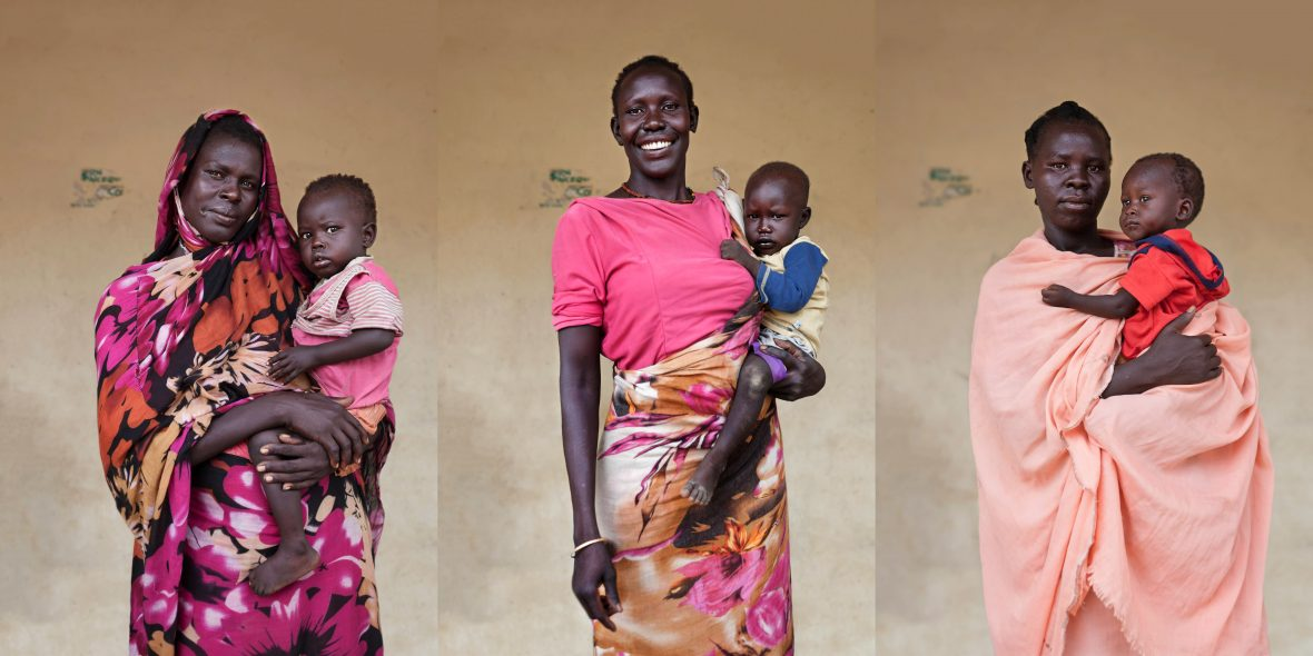 Three South Sudanese women with their infants, all wearing shades of pink